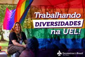 """Do lado esquerdo da foto tem uma bandeira com arco-íris e na frente uma mulher com lenço do JamCam e lenço da Diversidades. No canto direito há um filtro em arco-íris com o texto em branco """"Trabalhando diversidades na UEL!"""". No canto inferior direito o logo Escoteiros do Brasil São Paulo."""