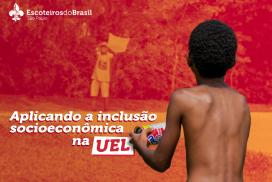 Ao fundo da foto há árvores e um menino de boné, camiseta e bermuda com uma pipa nas mãos. Em destaque, um menino negro está de costas e segura com a mão esquerda uma latinha com fio enrolado. No canto superior esquerdo da foto o logo dos Escoteiros do Brasil São Paulo e o abaixo o texto: Aplicando a inclusão socioeconômica na UEL.